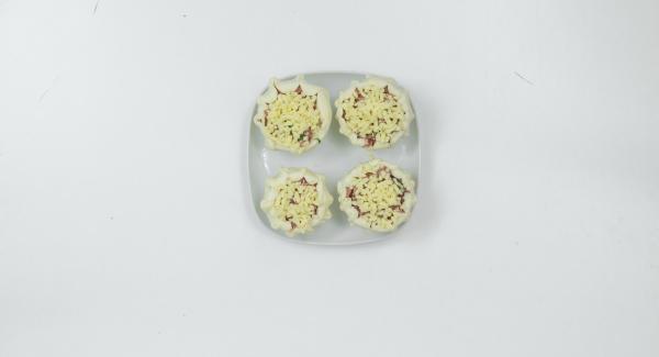 Para el relleno, picar el salami con perejil en un Quick Cut. Añadir la mitad del queso y volver a picar. Rellenar los tomates con la masa y añadir el queso restante en la parte superior.