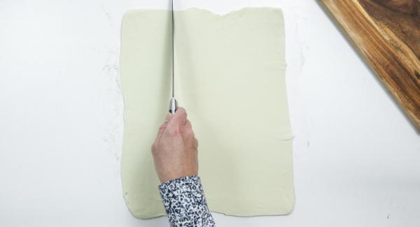 Extender la masa de hojaldre sobre una superficie de trabajo enharinada y cortarla en doce cuadrados de 10 x 10 cm.
