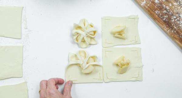 Poner unos dados de pera en el centro y doblar los bordes de la masa sobre las peras como una flor y presionarlas un poco (ver foto).