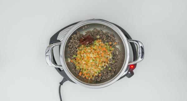 Agregar la mezcla de vegetales y cebolla y dorar. Añadir la salsa de tomate y rehogar. Agregar los tomates picados y el caldo y mezclar bien.