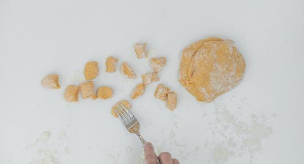Sobre una superficie de trabajo previamente enharinada, formar rollos de masa, que luego cortaremos en trozos pequeños y enrollaremos con un tenedor hasta obtener la forma típica de ñoquis.