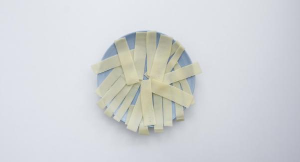 Cortar el jamón en rodajas muy finas y el queso en tiras.
