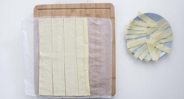 Extender la masa de hojaldre y cortar en 5 tiras. Colocar el queso en la mitad de la masa y a continuación las lonchas de jamón, dejando que sobresalgan un poco.