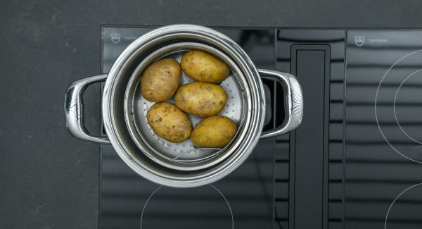 Verter una taza de agua en una olla. Lavar bien las patatas y colocarlas en la Softiera, introducir en la olla y tapar con la con la Tapa Rápida (Secuquick Softline).