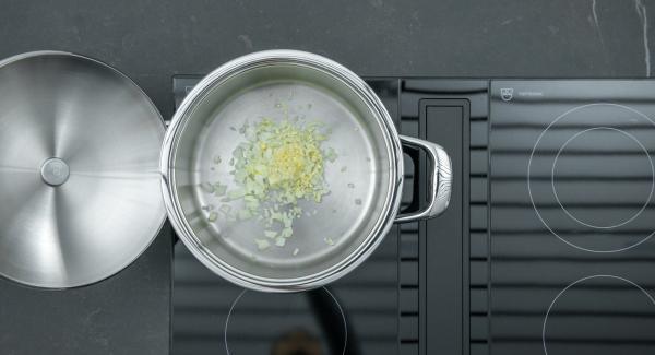 """Poner la cebolla y el ajo en una olla. Colocar la olla en el fuego a temperatura máxima. Encender el Avisador (Audiotherm), colocarlo en el pomo (Visiotherm) y girar hasta que se muestre el símbolo de """"chuleta""""."""