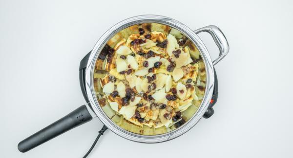 """Volver a tapar y cocinar por el otro lado hasta que se vuelta a llegar al símbolo de """"chuleta"""". Romper la masa en trozos pequeños. Agregar las manzanas, los arándanos y el azúcar moreno. Caramelizar levemente."""