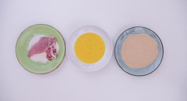 Enharinar los filetes de ternera, bañarlos en los huevos batidos y rebozarlos con el pan rallado.
