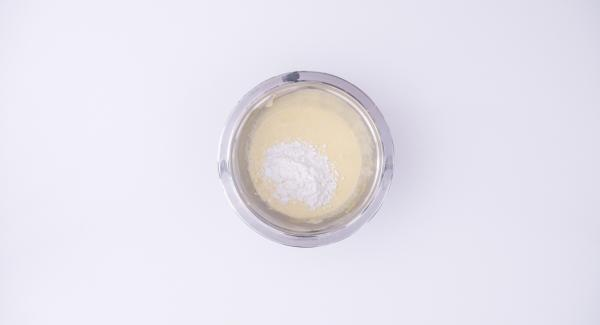 Mientras tanto, con una batidora, batir las 4 yemas de huevo con 150 g de azúcar hasta que la mezcla esté clara y espumosa. Incorporar la harina de maíz y mezclarlo todo bien hasta que no queden grumos.