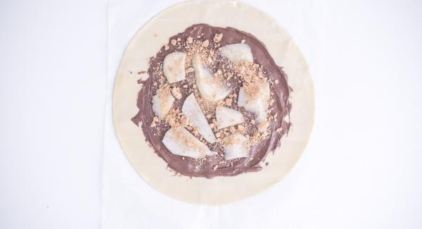 Cortar las peras en rodajas. Desmenuzar las galletas con el Quick Cut. Extender la pasta de hojaldre, untar el centro con Nutella, colocar la pera encima y decorar con las galletas desmenuzadas. Sellar la pasta de hojaldre como si fuera una gran empanadilla.