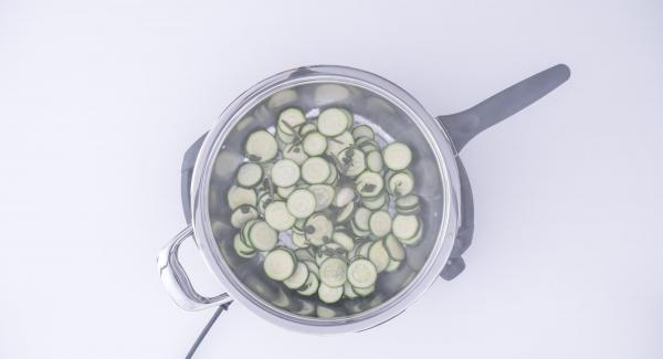Cuando el Avisador (Audiotherm) emita un pitido al finalizar el tiempo de cocción, retirar la tapa y dejar que el agua se evapore. Añadir el aceite y salterar los calabacines hasta que estén dorados. Retirar el ajo y servir.