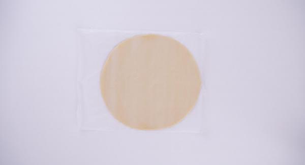 Extender el hojaldre en forma de círculo con un diámetro de unos 30 cm. Cortar un trozo de papel de horno del mismo diámetro.