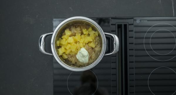 Dejar despresurizar la Tapa Rápida (Secuquick Softline) pulsando el botón amarillo y retirar. Añadir los dados de piña y la nata sazonando al gusto.