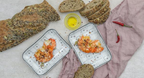 Colocar las brochetas de gambas en un plato, rociar con aceite de oliva y espolvorear con la guindilla picada.