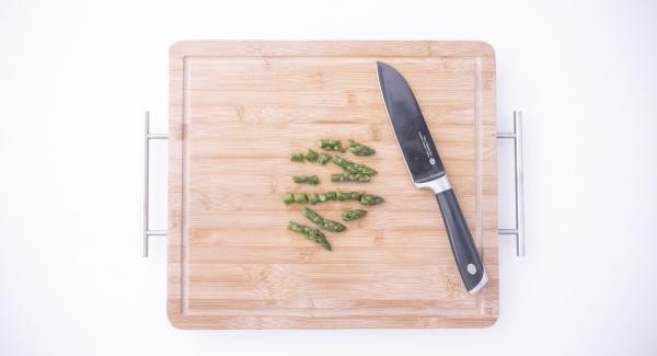"""Separar las puntas de los espárragos y cortar los tallos a trozos de unos 3 cm. Verter agua (unos 100 ml) en la olla. Colocar los espárragos troceados en la Softiera, introducir en la olla y tapar. Colocar la olla en el Navigenio a temperatura máxima (nivel 6). Encender el Avisador (Audiotherm), colocarlo en el pomo (Visiotherm) y girar hasta que se muestre el símbolo de """"zanahoria""""."""
