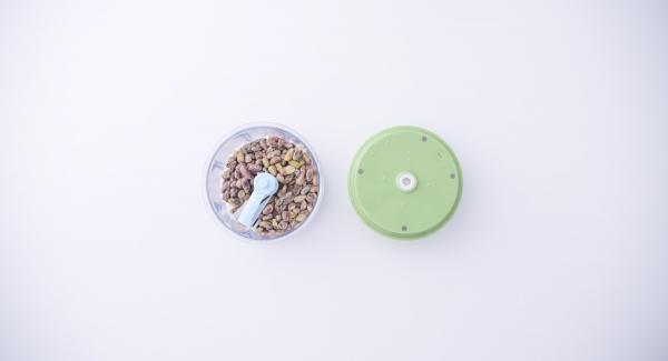 """Triturar los pistachos en el Quick Cut. Pelar el ajo, introducirlo en la sartén y tapar. Colocar la sartén en el Navigenio a temperatura media (nivel 4). Encender el Avisador (Audiotherm), colocarlo en el pomo (Visiotherm) y girar hasta que se muestre el símbolo de """"chuleta""""."""