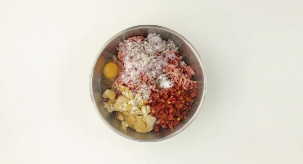Desmenuzar el panecillo en trocitos, amasarlo bien junto con la carne picada y los demás ingredientes