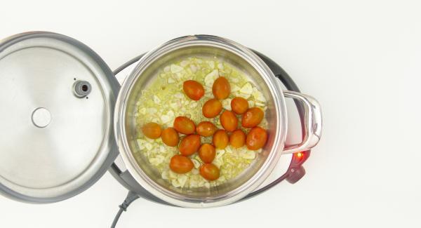 """Cuando el Avisador (Audiotherm) emita un pitido al llegar a la ventana de """"chuleta"""", bajar temperatura de Navigenio (nivel 2), remover y añadir el ajo y 6 cucharadas de aceite. Sofreír brevemente y añadir los tomate cherry enteros."""