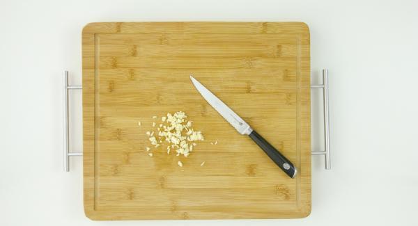 Picar el ajo y cortar el pescado en cubos.