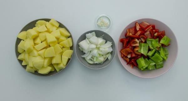 Pelar y cortar las patatas en cubos. Lavar y cortar los pimientos, también la cebolla y el ajo.