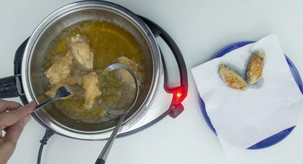 Secar a un papel absorbente y sazonar con sal. Añadir seguido la otra tanda de alitas y freírlas manteniendo la temperatura (Navigenio 4).