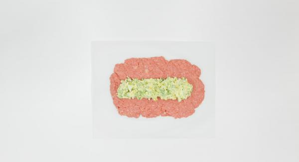 Presionar la carne picada sobre una hoja de papel de hornear en un rectángulo. Colocar la mezcla de huevo en el centro como una tira ancha, enrollarla y apretarla bien en los bordes para que el relleno quede bien cerrado. La masa debe tener ahora unos 20 cm de ancho.