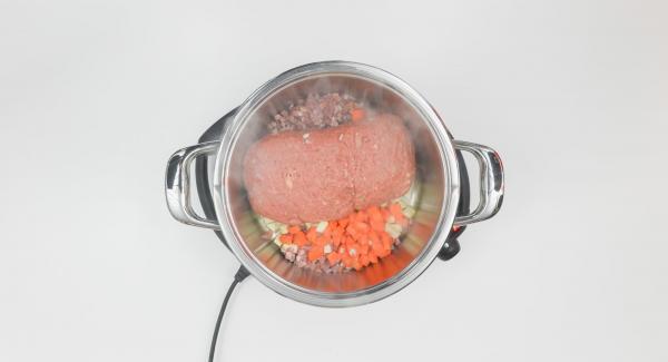 """Cuando el Avisador (Audiotherm) emita un pitido al llegar a la ventana de """"chuleta"""", bajar temperatura de Navigenio (nivel 2) y colocar el pastel de carne con la ayuda del papel. Añadir el bacon y los dados de verduras, freír brevemente y añadir el caldo."""