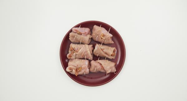 Distribuir la mezcla de carne picada sobre la carne, enrollar y fijar con un palillo.