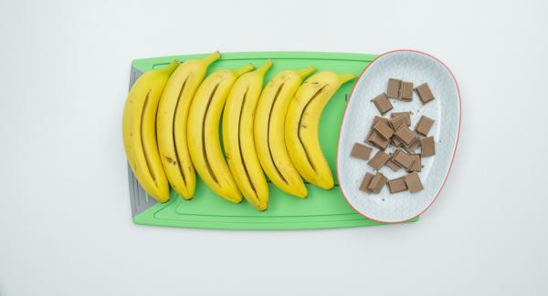 Lavar y secar bien los plátanos sin pelarlos. Hacer un corte a lo largo, a los plátanos con un cuchillo lo suficientemente profundo para rellenarlo con el chocolate. (el chocolate no debe sobresalir de la abertura).
