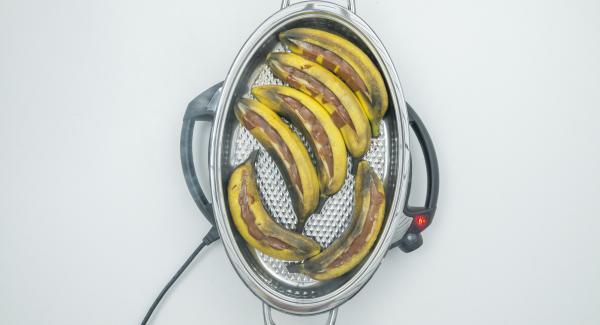 Asar con la ayuda Avisador (Audiotherm) hasta alcanzar la temperatura de 90 °C. Quitar la tapa, sacar los plátanos, quitar la cáscara y cortar los lados.