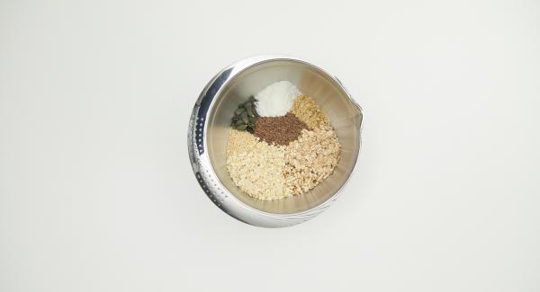 Poner las nueces en el QuickCut, cortarlas en trozos grandes y colocarlas en un recipiente con todos los ingredientes, incluidos los copos de espelta.