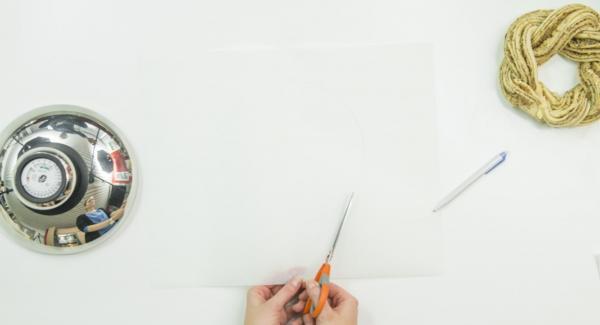 Con ayuda de una tapa de 20 cm cortar un círculo en papel de hornear y colocarlo en la olla. Cortar el rollo de masa longitudinalmente por la mitad y trenzar ambas mitades una alrededor de la otra con las superficies cortadas hacia arriba. Cerrar el círculo presionando bien los extremos.