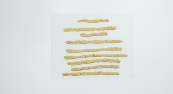 Con ayuda de la tapa oval cortar un óvalo de papel de hornear 2 cm más ancho que la base. Extender 3/4 de la masa sobre papel de horno (preferiblemente con las manos). Dividir el resto de la masa en 8 trozos y formar tiras para decorar.