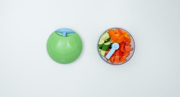 Limpiar los pimientos y el calabacín, picarlos finamente en el Quick Cut y colocarlos en una olla. Pelar la cebolla, picarla finamente y esparcirla sobre las verduras.