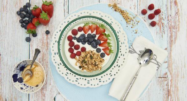 Mezclar el yogur con el muesli crujiente y decorar con los frutos rojos