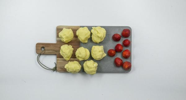 Dividir la masa en ocho porciones, formar tortitas y envolver cada fresa con ellas hasta obtener una bola.