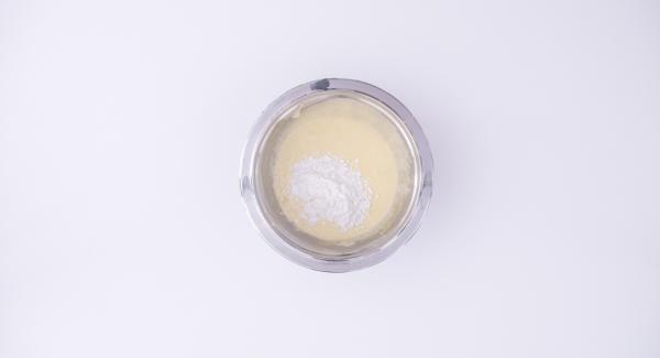 Mientras tanto, batir 4 yemas de huevo con el azúcar hasta obtener una mezcla clara y esponjosa. Añadir la maizena y mezclar bien para que no queden grumos.