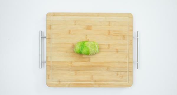 Extender la mezcla de carne picada sobre las hojas de repollo y enrollarlas, fijarlas con hilo de cocina.