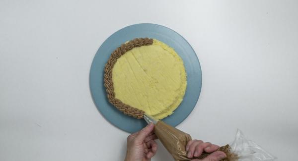 Batir la crema de chocolate a punto de nieve con un batidor Decorar el pastel con la ayuda de una manga pastelera.