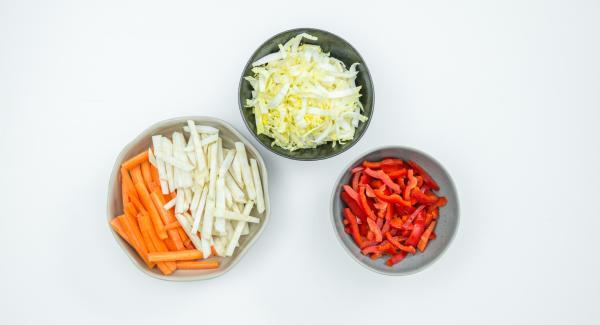 Pelar las zanahorias y el apio y cortarlos en tiras finas. Limpiar la col china y los pimientos y cortarlos en tiras finas.
