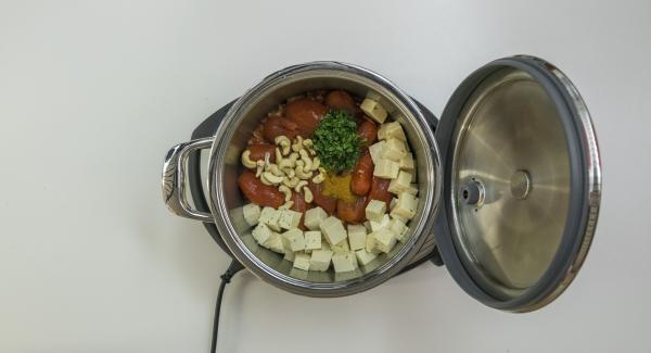 Añadir los tomates, el Garam Masala, los anacardos y la menta. Añadir también el tofu.