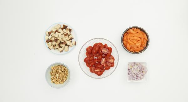 Pelar las chalotas, las zanahorias y los tomates. Cortar los chalotes en anillos finos. Cortar los tomates por la mitad. Cortar las zanahorias en palitos. Cortar el tofu en dados y picar las nueces.