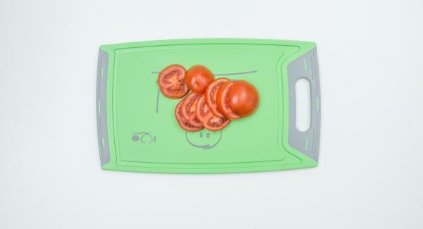 Lavar los tomates y cortar en rebanadas gruesas.