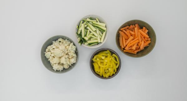Pelar las zanahorias, limpiar los calabacines y los pimientos y cortar todo en tiras. Limpiar la coliflor y dividirla en pequeños ramilletes.