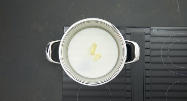 Colocar la olla en el fuego a temperatura máxima. Poner la  mantequilla, añadir la leche y el azúcar restante. Llevar a ebullición una vez y retirar del fuego.