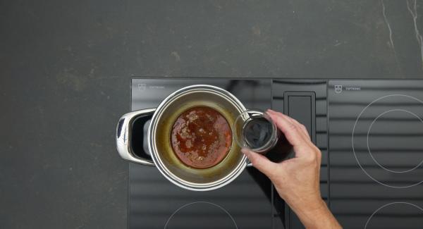 Mezclar el vino tinto y el agua y desglasar cuidadosamente el caramelo.