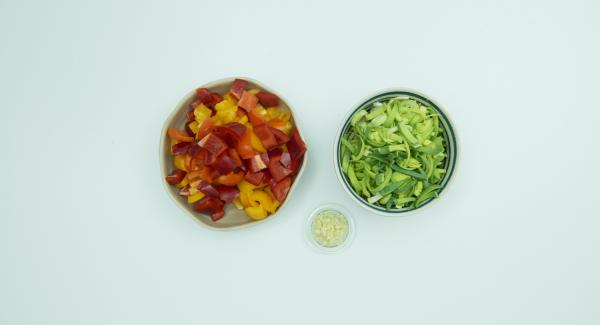 Limpiar el puerro, cortarlo longitudinalmente por la mitad y cortarlo transversalmente en tiras finas. Pelar y cortar el ajo finamente. Limpiar los pimientos y cortarlos en dados pequeños.