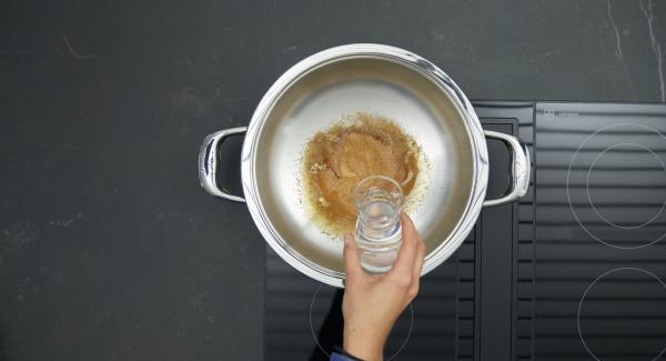 Retirar del fuego, añadir con cuidado el agua y cocinar a fuego lento hasta que el caramelo se haya disuelto.