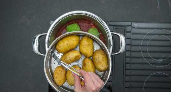 """Añadir la salsa de tomate. Colocar las patatas en la Softiera,  introducir en la olla y tapar con la Tapa Rápida (Secuquick Softline). Ajustar el fuego a temperatura baja cocinar en el símbolo de """"soft """"durante aproximadamente 10 minutos con el Avisador (Audiotherm)."""
