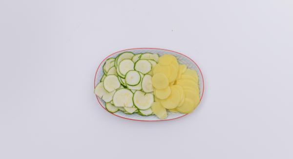 Limpiar el calabacín, pelar las patatas y cortarlas en rodajas finas.