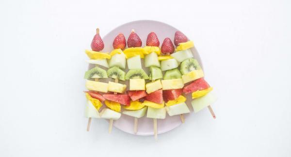 Pelar la fruta y cortarla en dados grandes. Insertar la fruta en una brocheta alternando las piezas y acabando con el fresón.